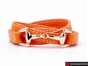 Oranje leren armband met gouden haak sluiting.